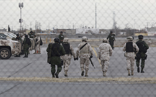 <div class='meta'><div class='origin-logo' data-origin='AP'></div><span class='caption-text' data-credit='AP Photo/Christian Torres'>Soldiers walk at the airport after the extradition of drug lord Joaquin &#34;El Chapo&#34; Guzman in Ciudad Juarez, Mexico, Thursday, Jan. 19, 2017</span></div>
