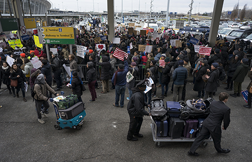 <div class='meta'><div class='origin-logo' data-origin='AP'></div><span class='caption-text' data-credit='AP Photo/Craig Ruttle'>People with luggage walk past protesters assembled at John F. Kennedy International Airport in New York, Saturday, Jan. 28, 2017.</span></div>