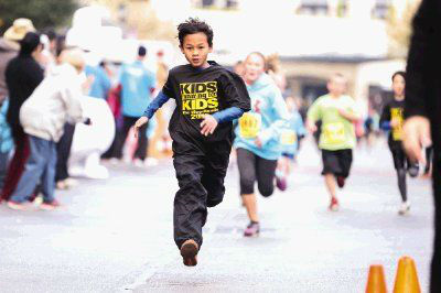 A runner crosses the finish line during the Kids Running for Kids fundraising event Saturday at Market Street in The Woodlands <span class=meta>Michael Minasi/HCN</span>