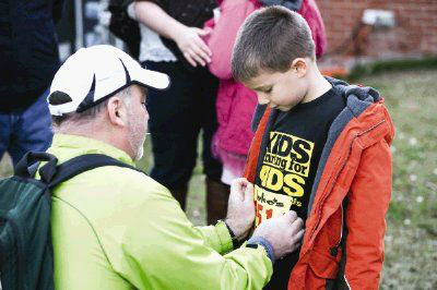 The Woodlands resident Todd Stephens pins a bib on his 6-year-old son, Owen, during the Kids Running for Kids fundraising event <span class=meta>Michael Minasi/HCN</span>