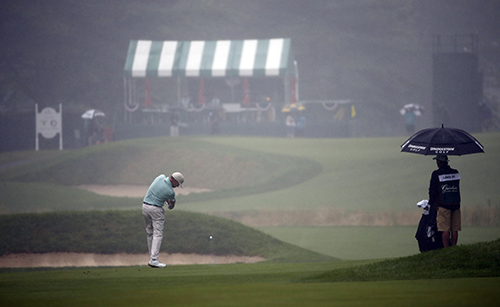 <div class='meta'><div class='origin-logo' data-origin='AP'></div><span class='caption-text' data-credit='AP Photo/Steve Helber'>Davis Love III hits his second shot to a fog and rain shrouded 12th green during the second round of the Greenbrier Classic golf tournament at the Greenbrier Resort.</span></div>