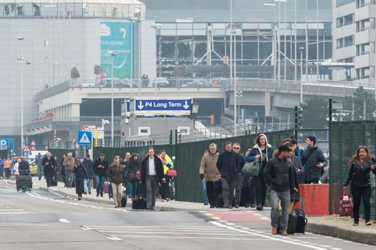 <div class='meta'><div class='origin-logo' data-origin='none'></div><span class='caption-text' data-credit='AP Photo/Geert Vanden Wijngaert'>People walk away from Brussels airport after explosions rocked the facility in Brussels, Belgium, Tuesday, March 22, 2016.</span></div>
