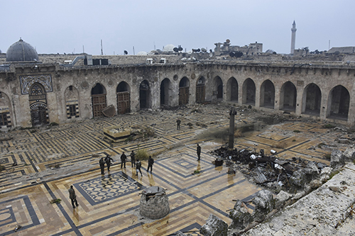 <div class='meta'><div class='origin-logo' data-origin='AP'></div><span class='caption-text' data-credit='SANA via AP'>Syrian troops and pro-government gunmen marching walk inside the destroyed Grand Umayyad mosque in the old city of Aleppo, Syria, Tuesday, Dec. 13, 2016.</span></div>
