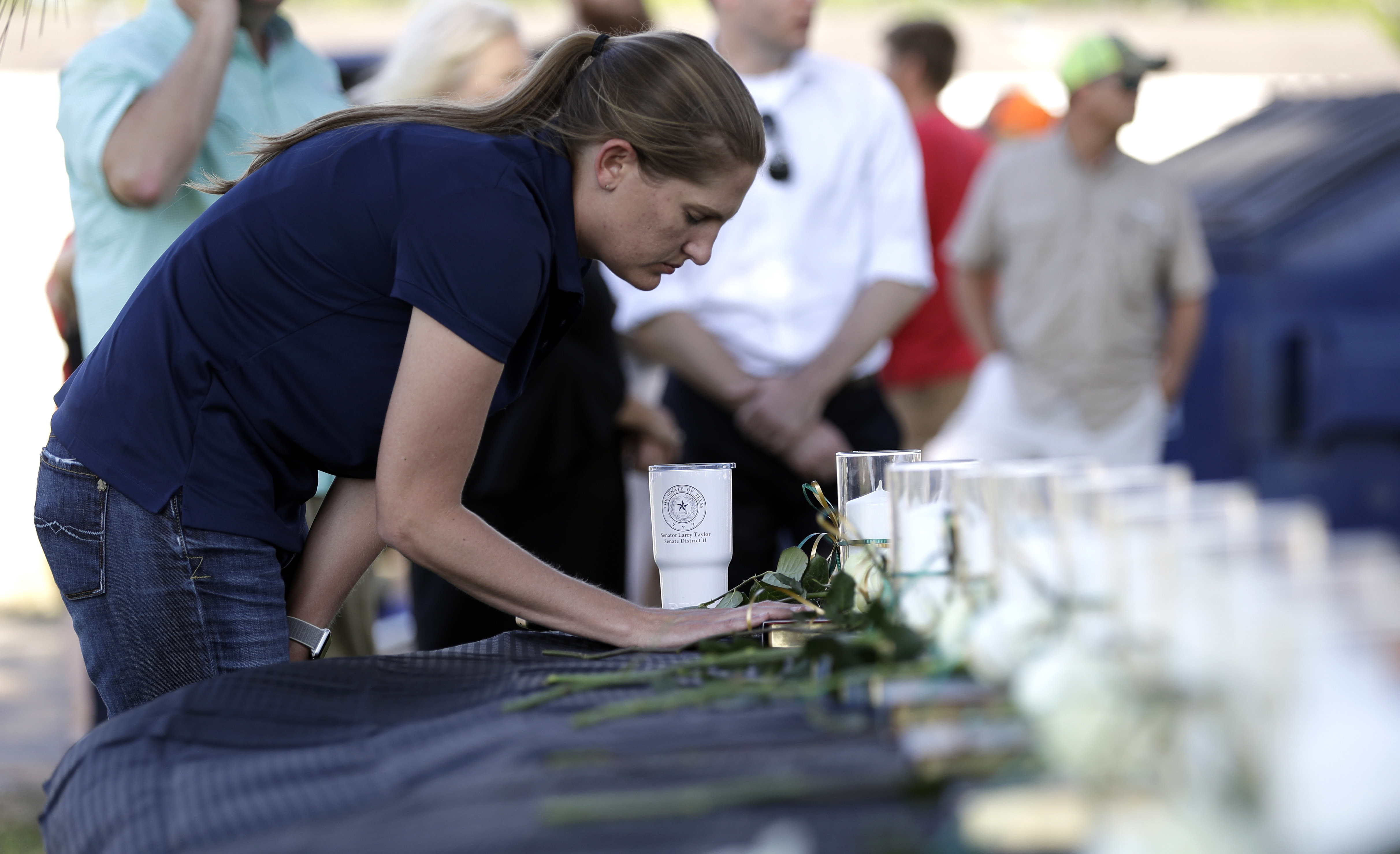 <div class='meta'><div class='origin-logo' data-origin='AP'></div><span class='caption-text' data-credit='AP'>A woman pauses at a table with 10 candles, roses and bibles displayed during a prayer vigil following a deadly shooting at Santa Fe High School. (AP Photo/David J. Phillip)</span></div>