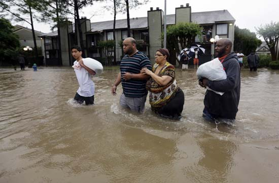 <div class='meta'><div class='origin-logo' data-origin='AP'></div><span class='caption-text' data-credit='AP Photo/David J. Phillip'>Darius Simon, second from left, helps his mother Carol, evacuate her flooded apartment complex along with his brother Dominique and son, Isaac Hernandez.</span></div>
