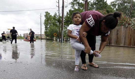 <div class='meta'><div class='origin-logo' data-origin='AP'></div><span class='caption-text' data-credit='AP Photo/David J. Phillip'>Brittany Parker puts a shoe back on her daughter Zoey after being rescued from their flooded apartment complex</span></div>
