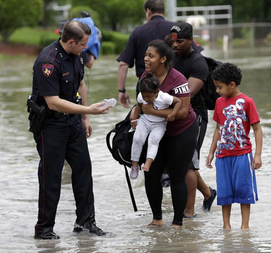 <div class='meta'><div class='origin-logo' data-origin='AP'></div><span class='caption-text' data-credit='AP Photo/David J. Phillip'>Harris County Constable Deputy J. King, left, hands a shoe to Brittany Parker as she holds her daughter Zoey</span></div>
