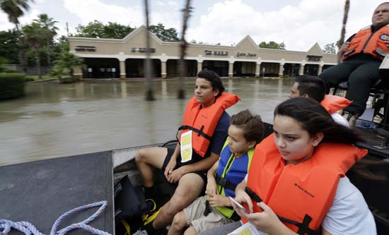 <div class='meta'><div class='origin-logo' data-origin='AP'></div><span class='caption-text' data-credit='AP Photo/David J. Phillip'>From left, Simon Holden, brother Phillip and sister Brianna ride in an airboat as they are evacuated</span></div>