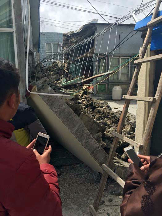 <div class='meta'><div class='origin-logo' data-origin='none'></div><span class='caption-text' data-credit='AP Photo/ Zhang Mao'>People stand near collapsed houses in Nyalam County of Xigaze Prefecture, southwest China's Tibet Autonomous Region</span></div>