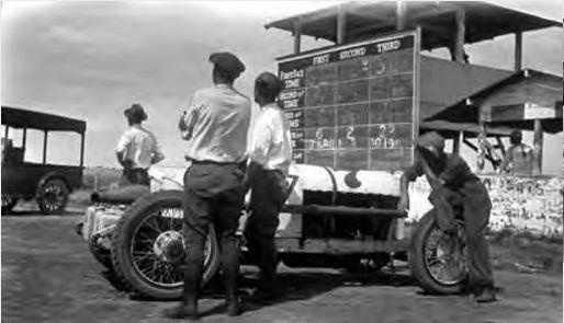 "<div class=""meta image-caption""><div class=""origin-logo origin-image ktrk""><span>KTRK</span></div><span class=""caption-text"">Four men standing beside a racecar. Beyond racecar is a scoreboard with spaces to show the racing time for first second and third racecars. (Houston Public Library)</span></div>"