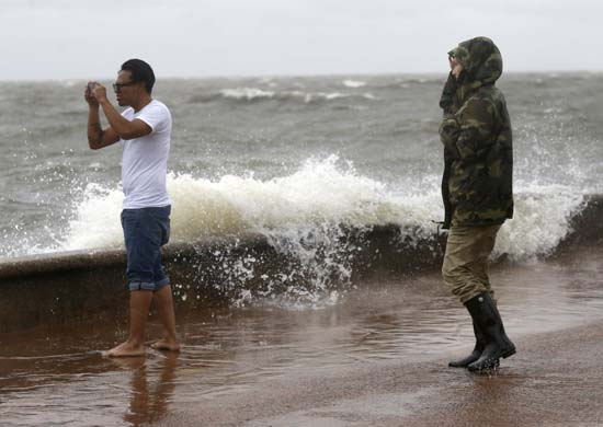 <div class='meta'><div class='origin-logo' data-origin='AP'></div><span class='caption-text' data-credit='Gerald Herbert'>Julie Plaisance, right, and Renee Davila take photos on the shore of Lake Pontchartrain as weather from T.S. Cindy, in the Gulf of Mexico, impacts the region in New Orleans.</span></div>