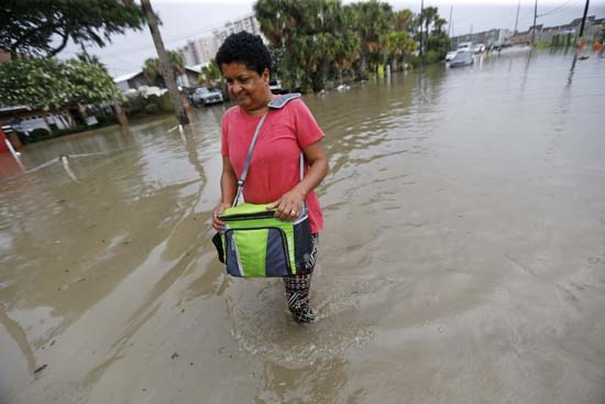 <div class='meta'><div class='origin-logo' data-origin='AP'></div><span class='caption-text' data-credit='Gerald Herbert'>Esther Martens walk through a flooded roadway to get to her car in the West End section of New Orleans, Wednesday, June 21, 2017.</span></div>