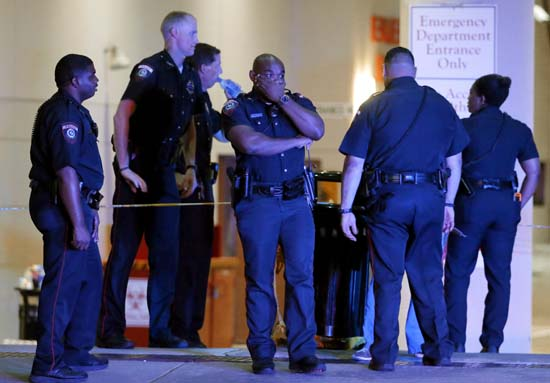 <div class='meta'><div class='origin-logo' data-origin='AP'></div><span class='caption-text' data-credit='AP Photo/Tony Gutierrez'>A Dallas police officer covers his face as he stands with others outside the emergency room at Baylor University Medical Center</span></div>