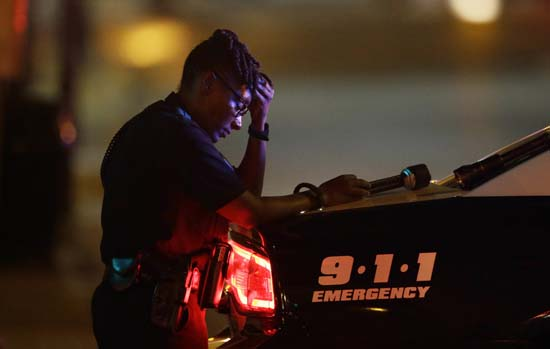 <div class='meta'><div class='origin-logo' data-origin='AP'></div><span class='caption-text' data-credit='AP Photo/LM Otero'>A Dallas police officer, who did not want to be identified, takes a moment as she guards an intersection in the early morning after a shooting in downtown Dallas</span></div>