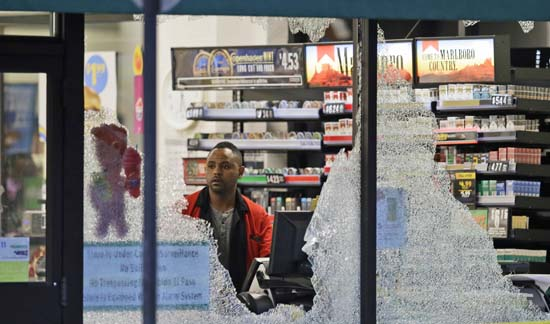 <div class='meta'><div class='origin-logo' data-origin='AP'></div><span class='caption-text' data-credit='AP Photo/LM Otero'>A clerk looks at broke windows shot out at a store in downtown Dallas</span></div>