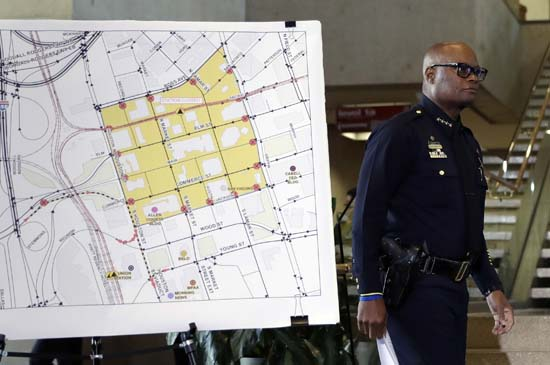 <div class='meta'><div class='origin-logo' data-origin='AP'></div><span class='caption-text' data-credit='AP Photo/Eric Gay'>Dallas police chief David Brown passes a map showing the area of downtown that remains a crime scene during a news conference</span></div>