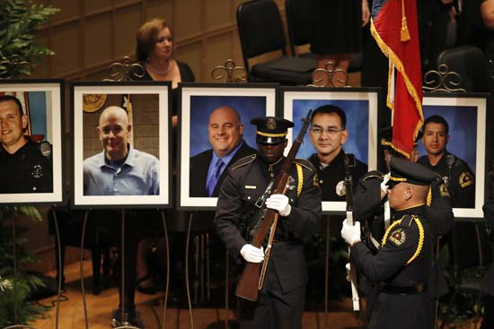 <div class='meta'><div class='origin-logo' data-origin='AP'></div><span class='caption-text' data-credit='AP Photo/Eric Gay'>Portraits of the five fallen police officers are seen at rear as a memorial gets underway</span></div>