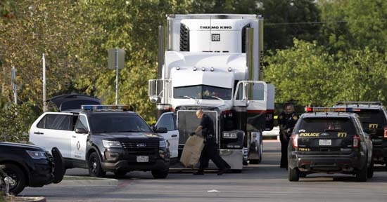 <div class='meta'><div class='origin-logo' data-origin='AP'></div><span class='caption-text' data-credit='Eric Gay'>San Antonio police officers investigate the scene where eight people were found dead in a tractor-trailer loaded with at least 30 others outside a Walmart store.</span></div>