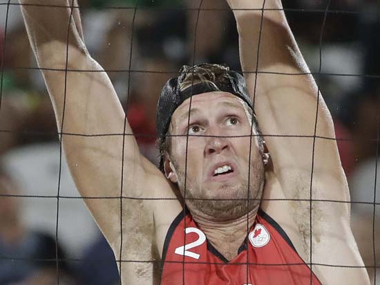 <div class='meta'><div class='origin-logo' data-origin='AP'></div><span class='caption-text' data-credit='AP Photo/Marcio Jose Sanchez'>Canada's Samuel Schachter attempts a block against Italy in a men's beach volleyball match</span></div>