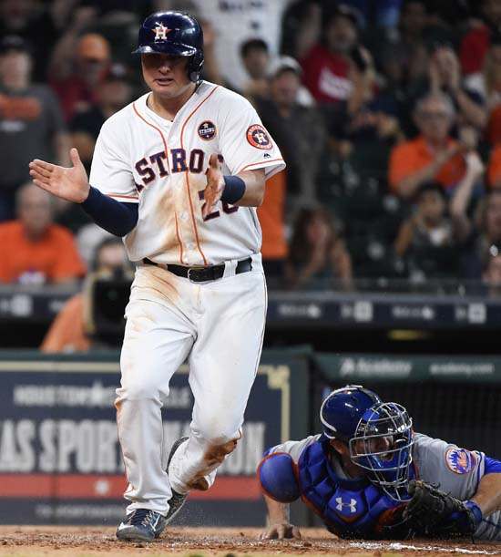 <div class='meta'><div class='origin-logo' data-origin='AP'></div><span class='caption-text' data-credit='Eric Christian Smith'>Houston Astros' J.D. Davis, left, celebrates beating the tag of New York Mets catcher Travis d'Arnaud to score a run on Tony Kemp's single during the seventh inning.</span></div>