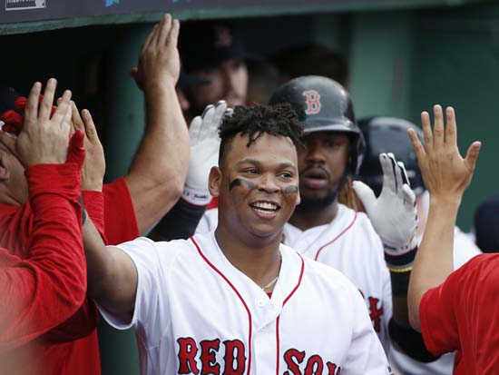 <div class='meta'><div class='origin-logo' data-origin='AP'></div><span class='caption-text' data-credit='Michael Dwyer'>Boston Red Sox's Rafael Devers, center, is congratulated by teammates in the dugout after his two-run home run against the Houston Astros during the third inning in Game 3</span></div>