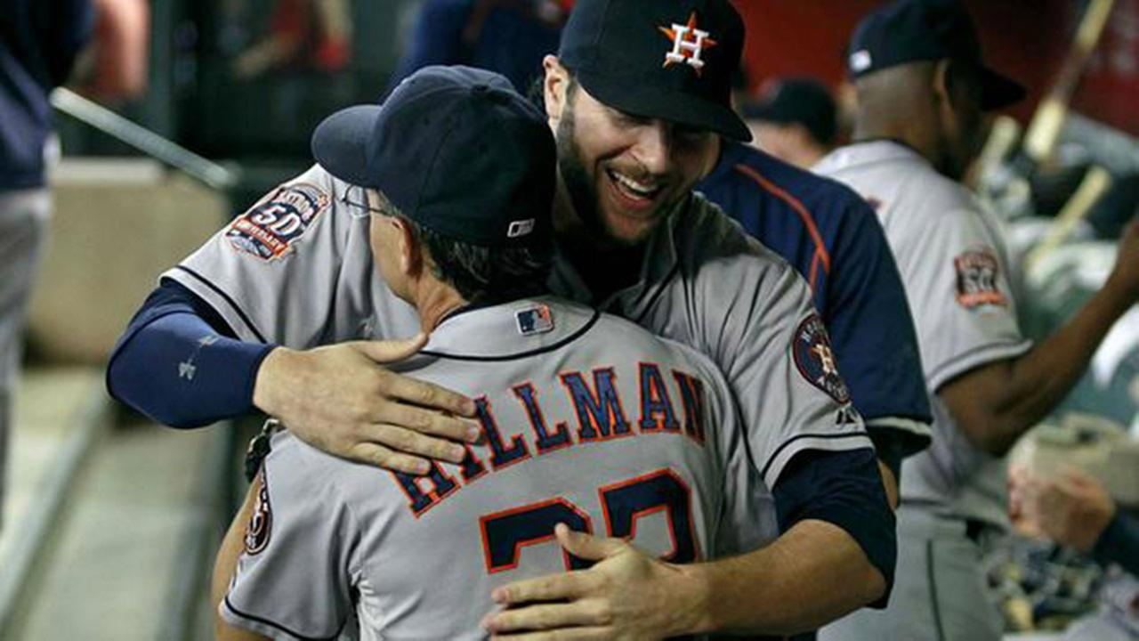 Houston Astros Jake Marisnick, right, embraces bench coach Trey Hillman during the start of a baseball game against the Arizona Diamondbacks.