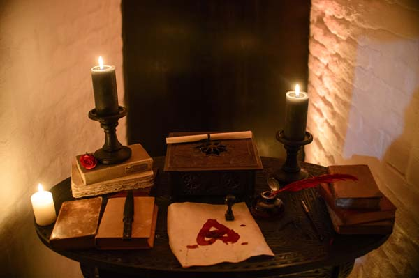 <div class='meta'><div class='origin-logo' data-origin='AP'></div><span class='caption-text' data-credit='AP Photo/Andreea Alexandru'>Candles and books are arranged on a table before a photo shoot of a room in Bran Castle, in Bran, Romania.</span></div>