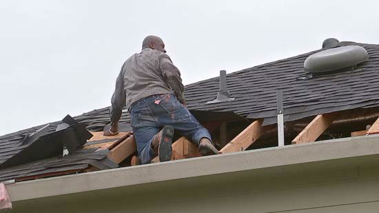 <div class='meta'><div class='origin-logo' data-origin='none'></div><span class='caption-text' data-credit='KTRK Photo'>A man covers a hole in his roof following severe storms in the Houston area</span></div>