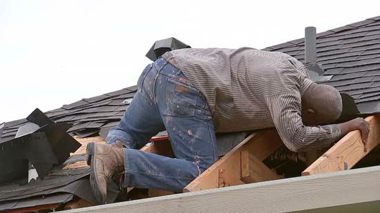 <div class='meta'><div class='origin-logo' data-origin='none'></div><span class='caption-text' data-credit='KTRK Photo'>A man surveys damage to a roof following severe storms in the Houston area</span></div>