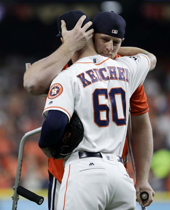 <div class='meta'><div class='origin-logo' data-origin='AP'></div><span class='caption-text' data-credit='AP'>Houston Texans' J.J. Watt, right, hugs Houston Astros pitcher Dallas Keuchel before throwing out the first pitch in Game 3. (AP Photo/Matt Slocum)</span></div>