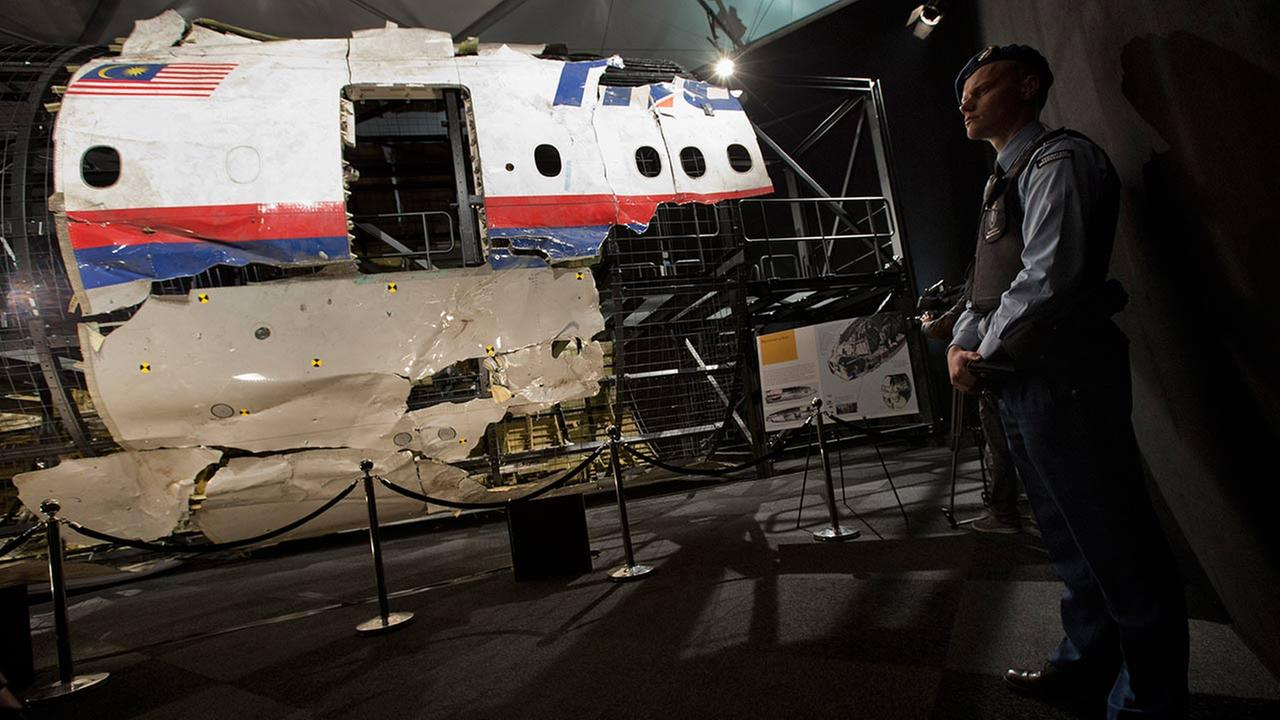 A Dutch Military Policeman stands guard next to a part of the reconstructed forward section of the fuselage of Malaysian Airlines Flight 17