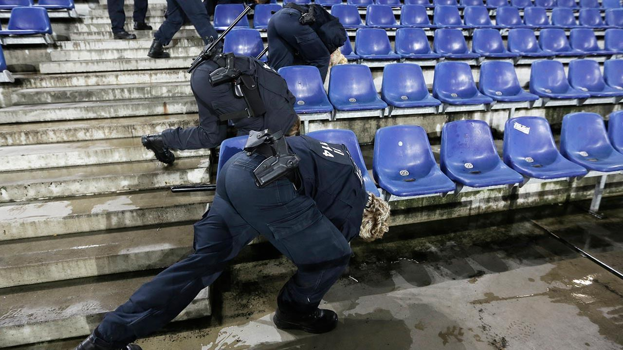 German police officers search between the seats of the stadium prior to an international friendly soccer match between Germany and the Netherlands in Hannover, Germany.