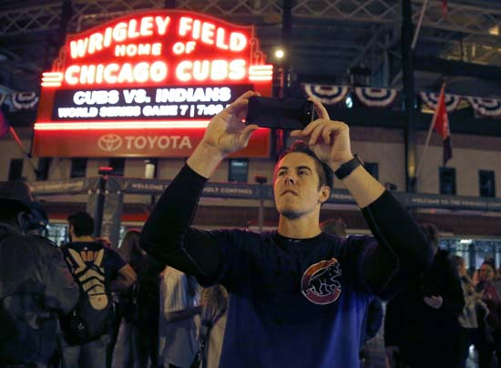<div class='meta'><div class='origin-logo' data-origin='AP'></div><span class='caption-text' data-credit='AP'>Chicago Cubs fan Jake Casper from Mount Prospect, Ill., photographs outside Wrigley Field in Chicago, shortly before the beginning of Game 7. (AP Photo/Charles Rex Arbogast)</span></div>