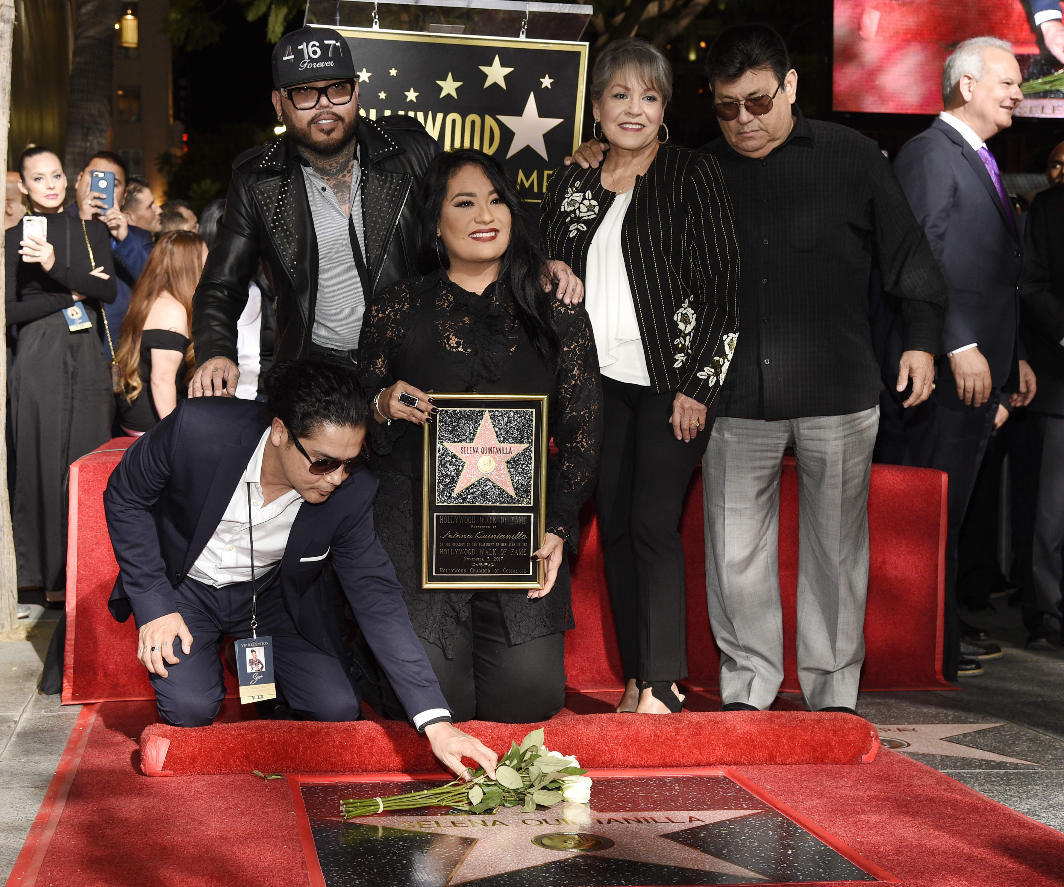 <div class='meta'><div class='origin-logo' data-origin='none'></div><span class='caption-text' data-credit='Chris Pizzello/Invision/AP'>Chris Perez, bottom left, the former husband of the late singer Selena Quintanilla, puts flowers down on her new star on the Hollywood Walk of Fame.</span></div>