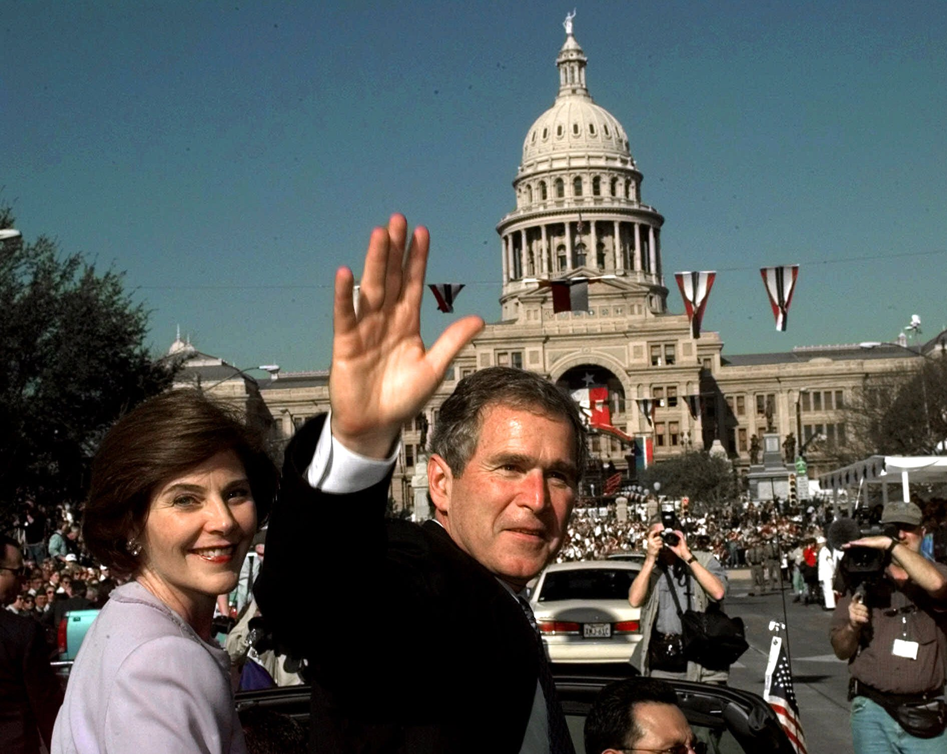 <div class='meta'><div class='origin-logo' data-origin='none'></div><span class='caption-text' data-credit='ASSOCIATED PRESS'>Texas Gov. George W. Bush, and his wife Laura ride in the inaugural parade with the Capitol in the background Tuesday, Jan. 19, 1999, in Austin, Texas.</span></div>