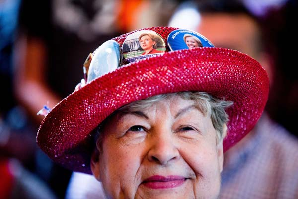 <div class='meta'><div class='origin-logo' data-origin='AP'></div><span class='caption-text' data-credit='AP Photo/Andrew Harnik'>A Hillary Clinton supporter wears campaign buttons on her hat</span></div>