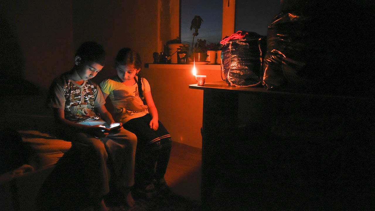 Ethnic Crimean tartar children play on a cell phone in candlelight at their home