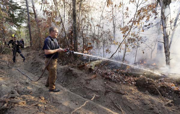 <div class='meta'><div class='origin-logo' data-origin='AP'></div><span class='caption-text' data-credit='AP Photo/Mark Humphrey'>Assistant Chief Brent Masey, of Highway 58 Fire Department in Harrison, Tenn., sprays water on a wildfire Thursday, Nov. 10, 2016, in Soddy-Daisy, Tenn.</span></div>