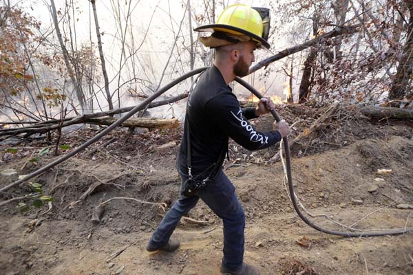 <div class='meta'><div class='origin-logo' data-origin='AP'></div><span class='caption-text' data-credit='AP Photo/Mark Humphrey'>Lieutenant Jesse Mooney, of the Flat Top Mountain Volunteer Fire Department, carries a hose as firefighters battle a wildfire</span></div>