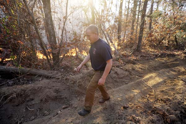 <div class='meta'><div class='origin-logo' data-origin='AP'></div><span class='caption-text' data-credit='AP Photo/Mark Humphrey'>Assistant Chief Brent Masey, of the Highway 58 Fire Department in Harrison, Tenn., walks along a firebreak</span></div>