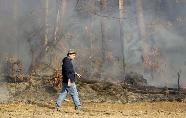 <div class='meta'><div class='origin-logo' data-origin='AP'></div><span class='caption-text' data-credit='AP Photo/Mark Humphrey'>David Benton walks past burning trees and brush at his home Thursday, Nov. 10, 2016, in Soddy-Daisy, Tenn.</span></div>