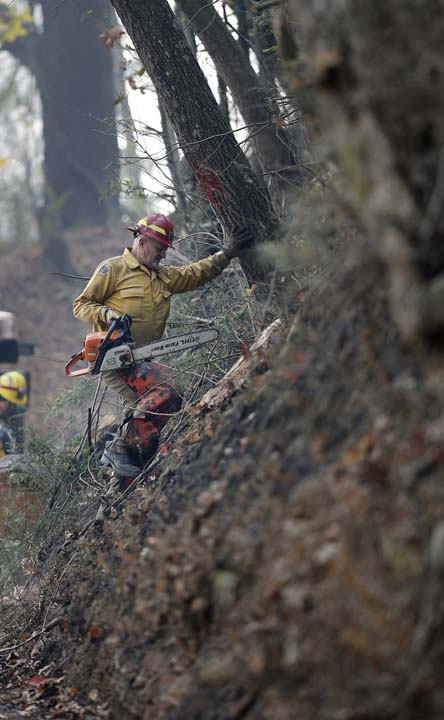 <div class='meta'><div class='origin-logo' data-origin='AP'></div><span class='caption-text' data-credit='AP Photo/John Bazemore'>Firefighter Ron Thalacker climbs a charred hill as he prepares to cut down a tree while fighting a wildfire Tuesday, Nov. 15, 2016, in Clayton, Ga.</span></div>