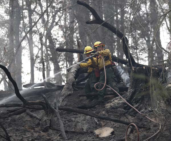 <div class='meta'><div class='origin-logo' data-origin='AP'></div><span class='caption-text' data-credit='AP Photo/John Bazemore'>Firefighters work to cool hot spots after a wildfire burned a hillside in Clayton, Ga.</span></div>