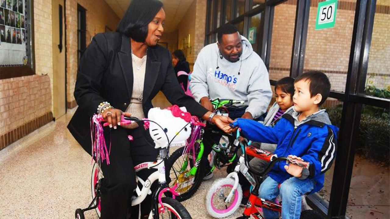 Bang Elementary School principal Erwann Wilson and former NFL star Rodney Hampton enjoy riding the new bicycles with two students Angelik Palomo and Adam Tran.