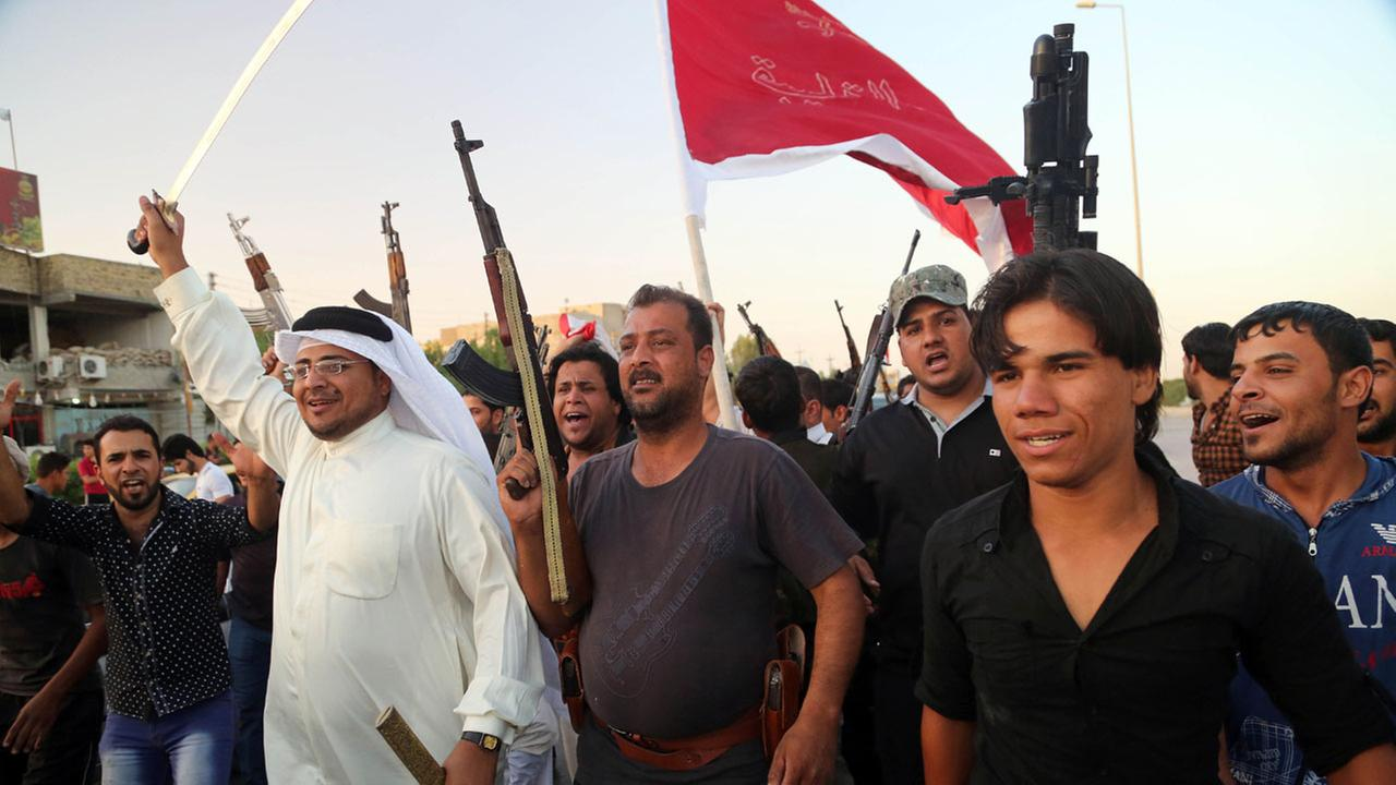 Shiite tribal fighters raise their weapons and chant slogans against the al-Qaida-inspired Islamic State of Iraq and the Levant in Basra on June 15, 2014.