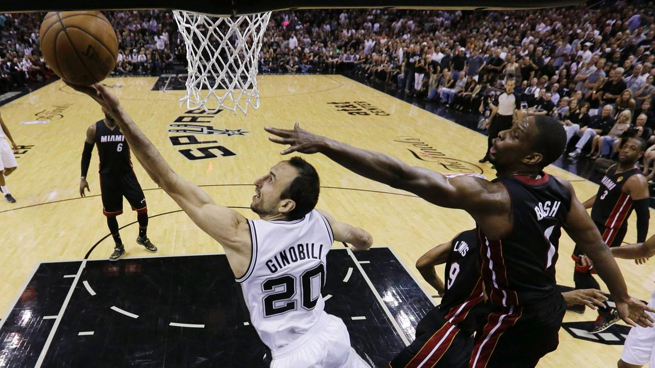 San Antonio Spurs guard Manu Ginobili (20) shoots as Miami Heat center Chris Bosh (1) defends during the first half in Game 5 of the NBA basketball finals on Sunday, June 15, 2014.