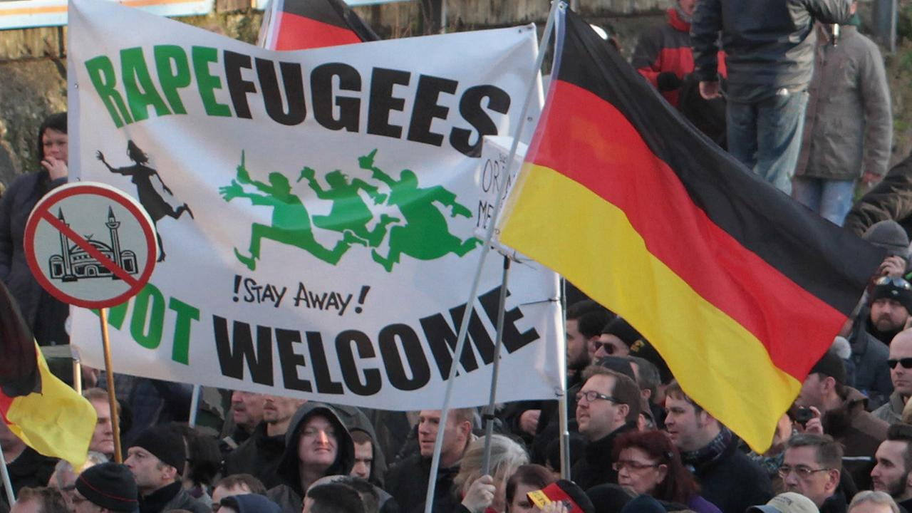 Right-wing demonstrators hold a sign Rapefugees not welcome - !Stay away!