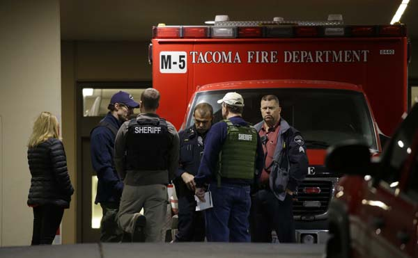 <div class='meta'><div class='origin-logo' data-origin='AP'></div><span class='caption-text' data-credit='AP Photo/Ted S. Warren'>Law enforcement officers gather in front of an ambulance at Tacoma General Hospital</span></div>