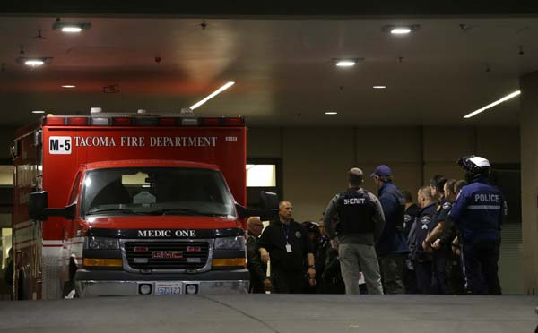 <div class='meta'><div class='origin-logo' data-origin='AP'></div><span class='caption-text' data-credit='AP Photo/Ted S. Warren'>Law enforcement officers gather next to an ambulance at Tacoma General Hospital</span></div>