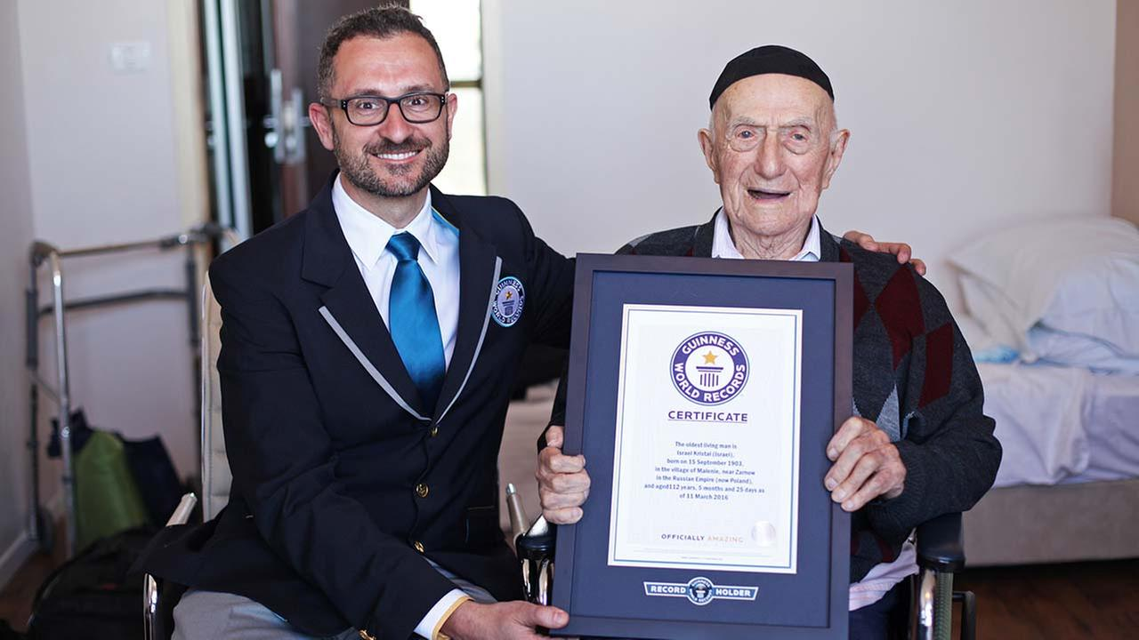 Marco Frigatti, Head of Records for Guinness World Records, left, presents Israel Kristal a certificate for being the oldest living man, in Haifa, Israel